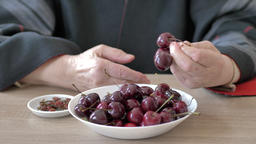 Hands of an old woman are taking sweet cherries from a plate Footage
