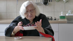 Funny old woman with a plate of sweet cherries Footage