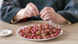 Closeup at an old woman hands eating red gooseberry Footage
