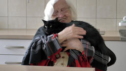 Old woman is hugging a black cat Footage