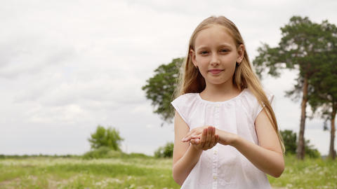 Cute teenager girl blowing daisy petals from palm hand to camera. Carefree young Footage