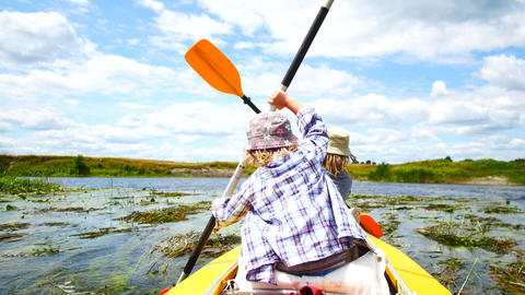 A child paddles on a kayak paddle. Active family vacation Footage