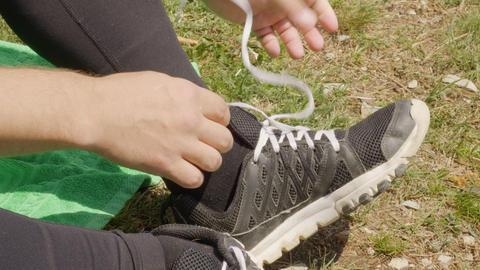 Male hands undoing shoelaces on sneakers while outdoor rest. Man unties laces on Footage