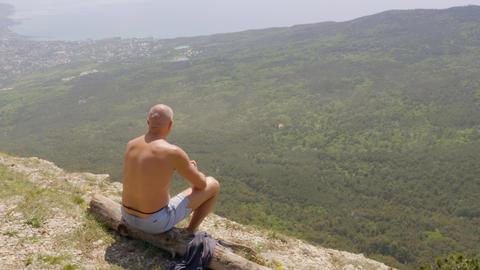 Adult man sitting on mountain edge, green valley and sea on horizon. traveling Footage