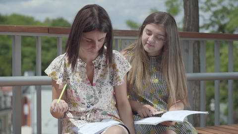 Two attractive female students sitting outdoors together discussing homework Footage