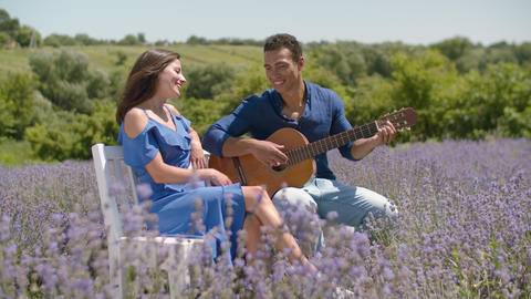 Man serenading his girlfriend with guitar in nature Footage