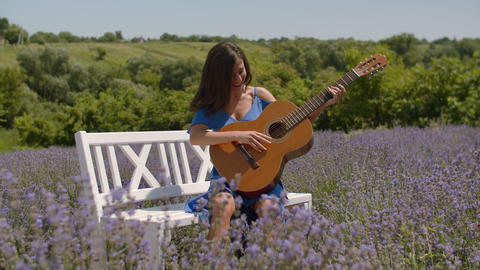 Positive smiling woman playing guitar in nature Footage