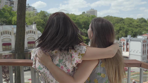 Two pretty girls standing outdoors together hugging and talking, admiring Footage