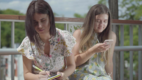 Two cute young woman students sitting outdoors together. One girl listening to Footage