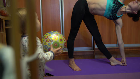 Mother makes yoga at home and little kid play arround Footage