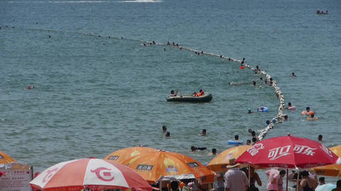 People swim in sea,A lot of people at crowded bathing beach.China's Qingdao City Footage