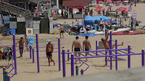 people playing exercises horizontal bar on beach.timelapse Stock Video Footage