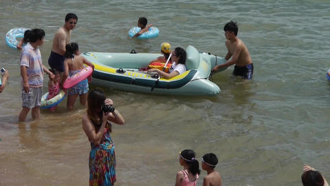 people at crowded bathing beach.People swim in sea,toys... Stock Video Footage