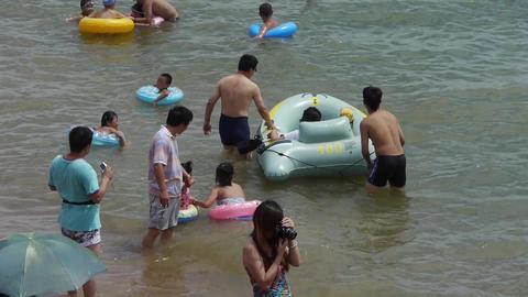 people at crowded bathing beach.People swim in sea,toys kayaking kayak inflatabl Footage