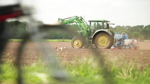 Tractor sowing on a ploughed agricultural field Footage