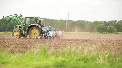 Tractor sowing on a ploughed agricultural field Stock Video Footage