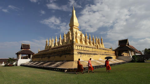Three monks walking in front of golden pagoda, Laos Footage
