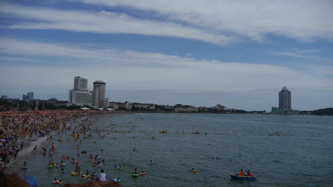 People swim in sea,A lot of people at crowded bathing sandy beach.Clouds in blue sky.Panoramic of Ch Footage