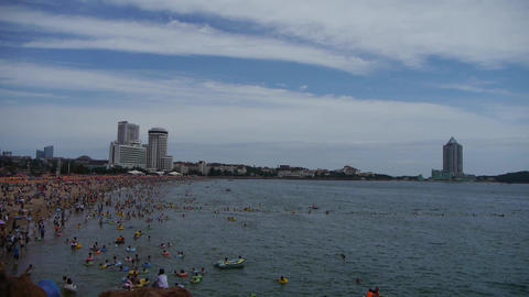 People swim in sea,A lot of people at crowded bathing sandy beach.Clouds in blue Footage