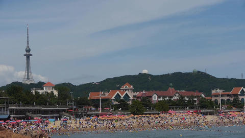 A lot of people at crowded bathing beach.China's Qingdao City.high tower on fore Footage