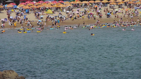 A lot of people at crowded bathing sandy beach.People swim in sea,China's Qingda Footage