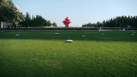 Red torch sculpture & Green grass.This public... Stock Video Footage