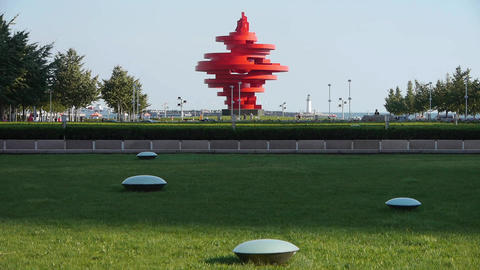 Red torch sculpture,Green grass & Seaside lighthouse.This public sculpture c Footage