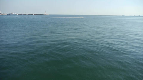 Water ripples surface.sea ocean wave.boat speeding on sea.Lighthouse on skyline Footage