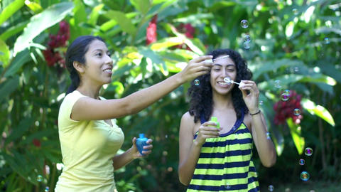 Young women blowing soap bubbles Footage