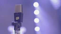 A microphone on a stage in the light of lights. Close-up Footage