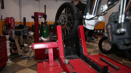 mechanic putting the front wheel on motorcycle, slider shot Footage
