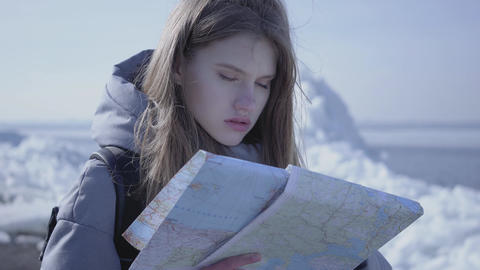 Portrait of young blond pretty woman in warm jacket standing on the glacier with Footage