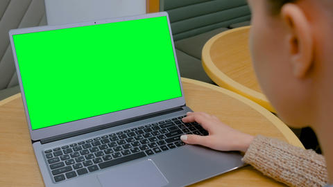 Woman looking at laptop computer with blank green screen in cafe Footage