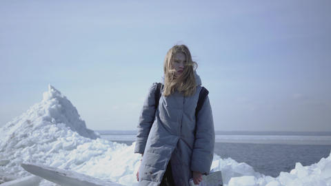 Cute young woman in warm jacket walking on the glacier, holding her cellphone in Footage