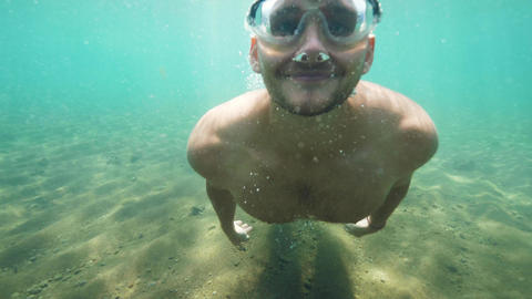 Happy young man traveller is diving underwater in mask in ocean on vacation Footage