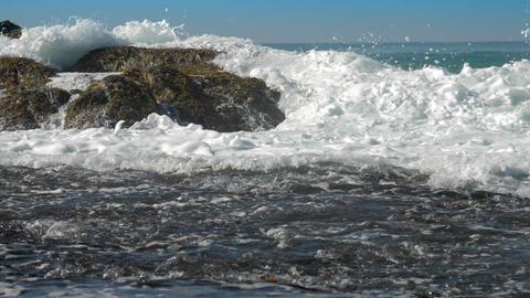 foaming ocean waves roll on brown rock near coastline Footage