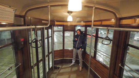 Man rides in old historical tram with wooden furniture and glass lamps in Milan Footage