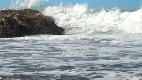 huge ocean waves crush into brown rock foaming slow Footage