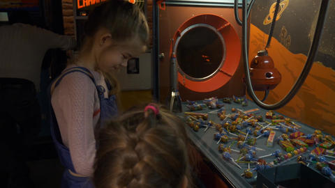 Two girls play with old fashioned slot machine trying to grab lollipops Footage
