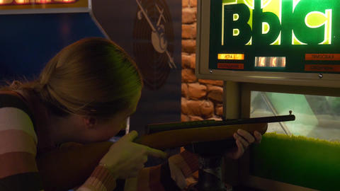 Blonde girl shoots with rifle in arcade game in museum of slot machines Footage