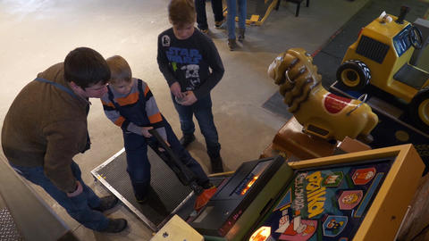 Father with sons try strength testing slot machine in museum of old arcade games Footage