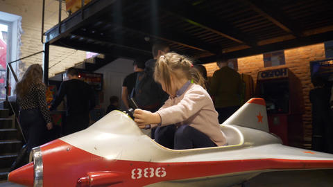 Small cute caucasian girl rides white and red fake plane in amusement park Footage