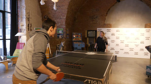 Male and female play table tennis in museum of old fashioned slot machines Footage