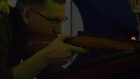 Young man in glasses shoots with rifle in arcade game in museum of slot machines Footage