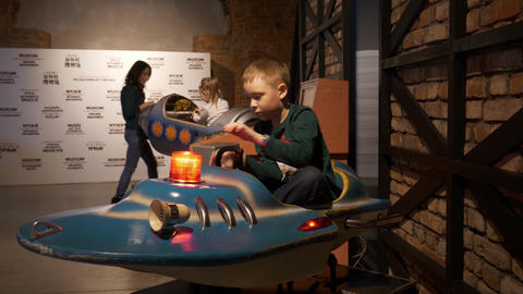 Cute caucasian boy sits on working blue fake rocket in arcade games museum Footage
