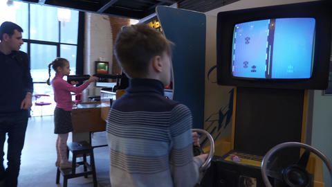 Active caucasian boy practices his skills on a car-racing slot machine in museum Footage