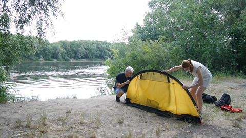 Father and daughter campers putting up tent. Green tourism, hiking. Happy Footage