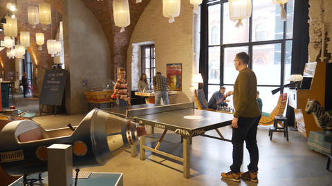 Caucasian guy and girl play table tennis in museum of old retro slot machines Footage