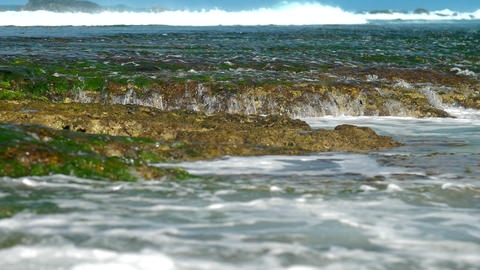 transparent ocean water flows over brown rocks slow motion Footage