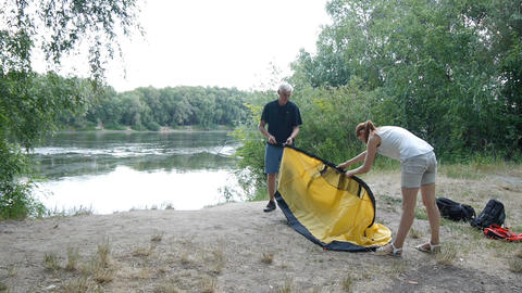 Campers putting up tent, preparing to overnight in wild, green tourism, hiking Live Action
